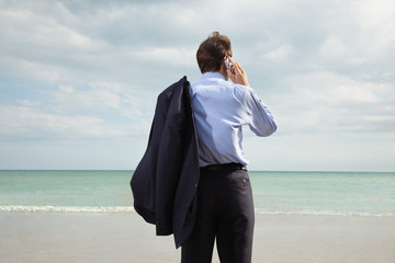 Businessman on beach using cell phone
