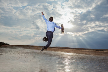 Businessman jumping on beach and looking at sky