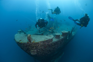 Silhouettes of scuba divers exploring the bow of a shipwreck.