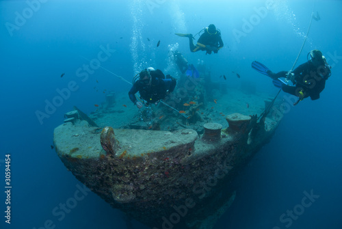 Silhouettes of scuba divers exploring the bow of a shipwreck. - 30594454