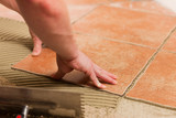 Tiler tiling tiles on the floor