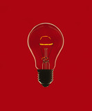 Glowing light bulb against red background