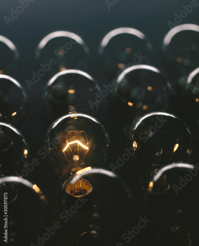 Glowing light bulb against dark background