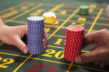 People placing bets with gambling chips