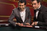 Men tossing dice at craps table