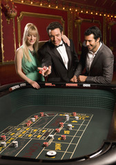 Man tossing dice at craps table with friends watching