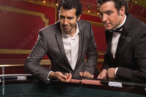 Men tossing dice at craps table