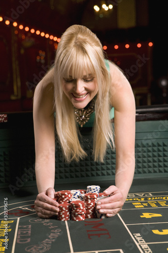 Woman gathering winnings at craps table