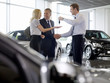 Salesman handing couple keys to new car in showroom