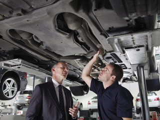 Businessman looking underneath car with mechanic