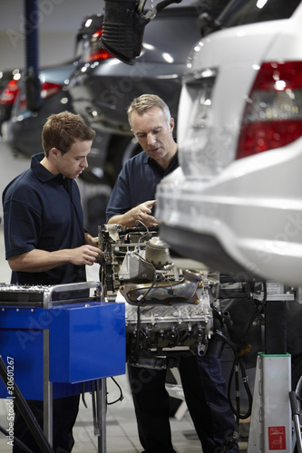 Mechanics working on engine in auto repair shop