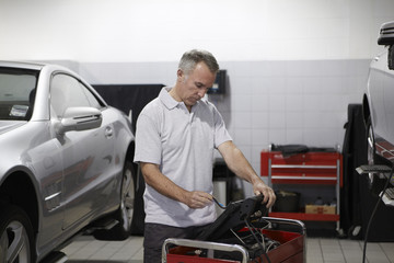 Mechanic working on computer in auto repair shop