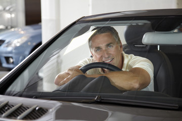 Man sitting in car in automobile showroom