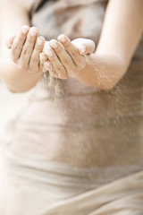 Close up of sand blowing out of a woman?s hands