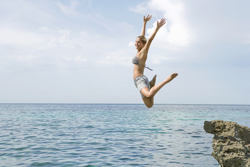 Excited woman jumping into ocean
