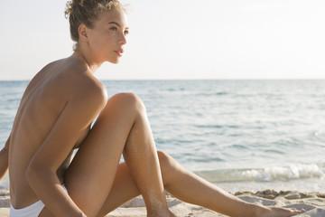 Topless woman sitting on beach
