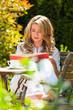 Frau beim Buch lesen im Garten