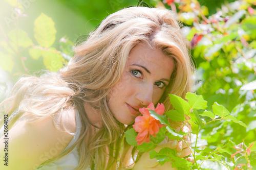 Frau riecht an einer Rose im Garten