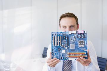 Businessman holding circuit board
