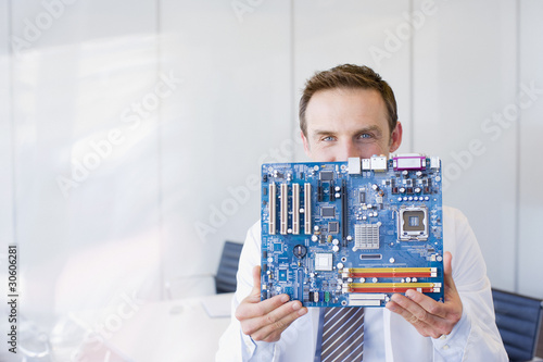 Businessman holding circuit board