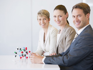 Business people in conference room with molecule model