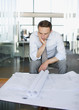 Businessman looking at blueprint in office