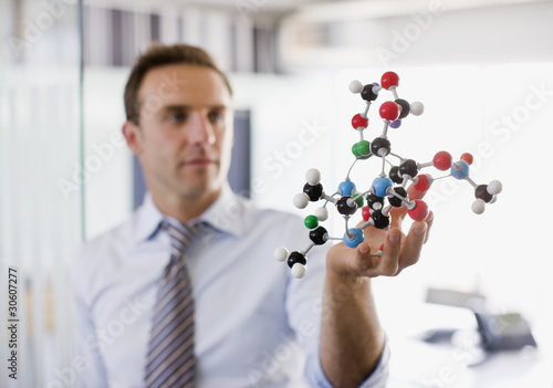 Businessman holding molecule model in office