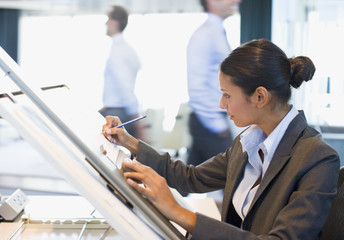 Businesswoman drawing on drafting table in office