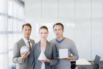 """Business people holding a sphere, cube and cone"""