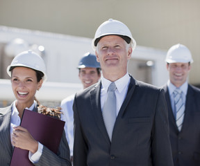 Business people in hard-hats standing together outdoors
