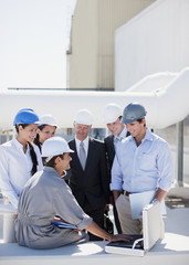 Worker talking to business people in hard-hats outdoors