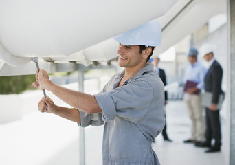 Worker in hard-hat adjusting bolt on large pipe outdoors