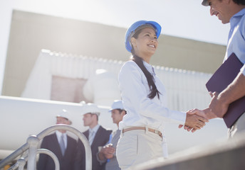 Businesswoman shaking hands with worker outdoors