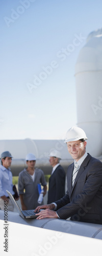 Businessman in hard-hat using laptop outdoors