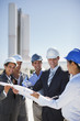 Business people in hard-hats reviewing blueprints outdoors