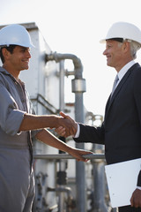 Businessman in hard-hat shaking hands with worker outdoors