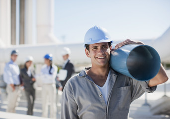 Worker in hard-hat carrying large pipe outdoors