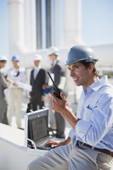 Businessman in hard-hat talking on walkie-talkie outdoors