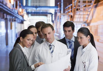 Business people and scientists looking at blueprints in factory