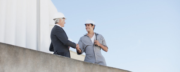 Businessman in hard-hat shaking hand with worker outdoors