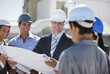 Business people and worker reviewing blueprints outdoors