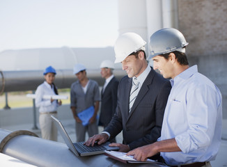Businessmen in hard-hats working on laptop outdoors