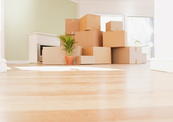 Boxes stacked on wooden floor of new house