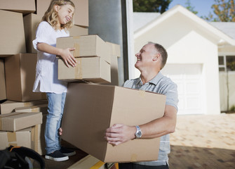 Father and daughter carrying boxed from moving van