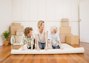 Mother and sons unrolling carpet in new house