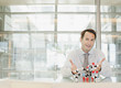 Businessman sitting at desk with molecule model