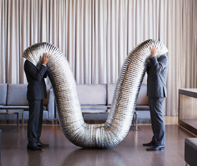 Businessmen with their heads inside metal tubing