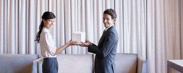 Business people holding white cube in hotel lobby