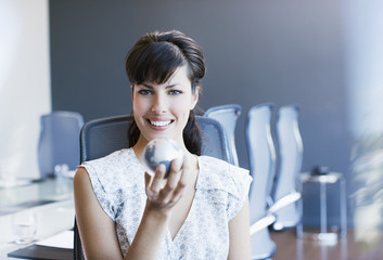 Businesswoman  holding small globe in conference room