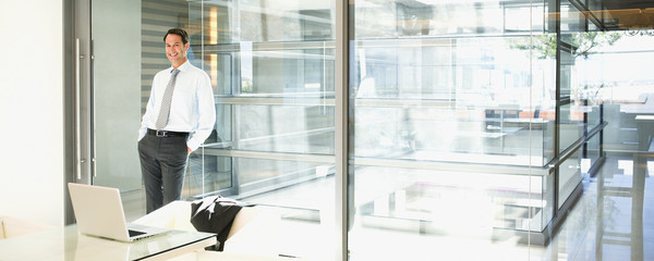 Businessman leaning against glass wall in office
